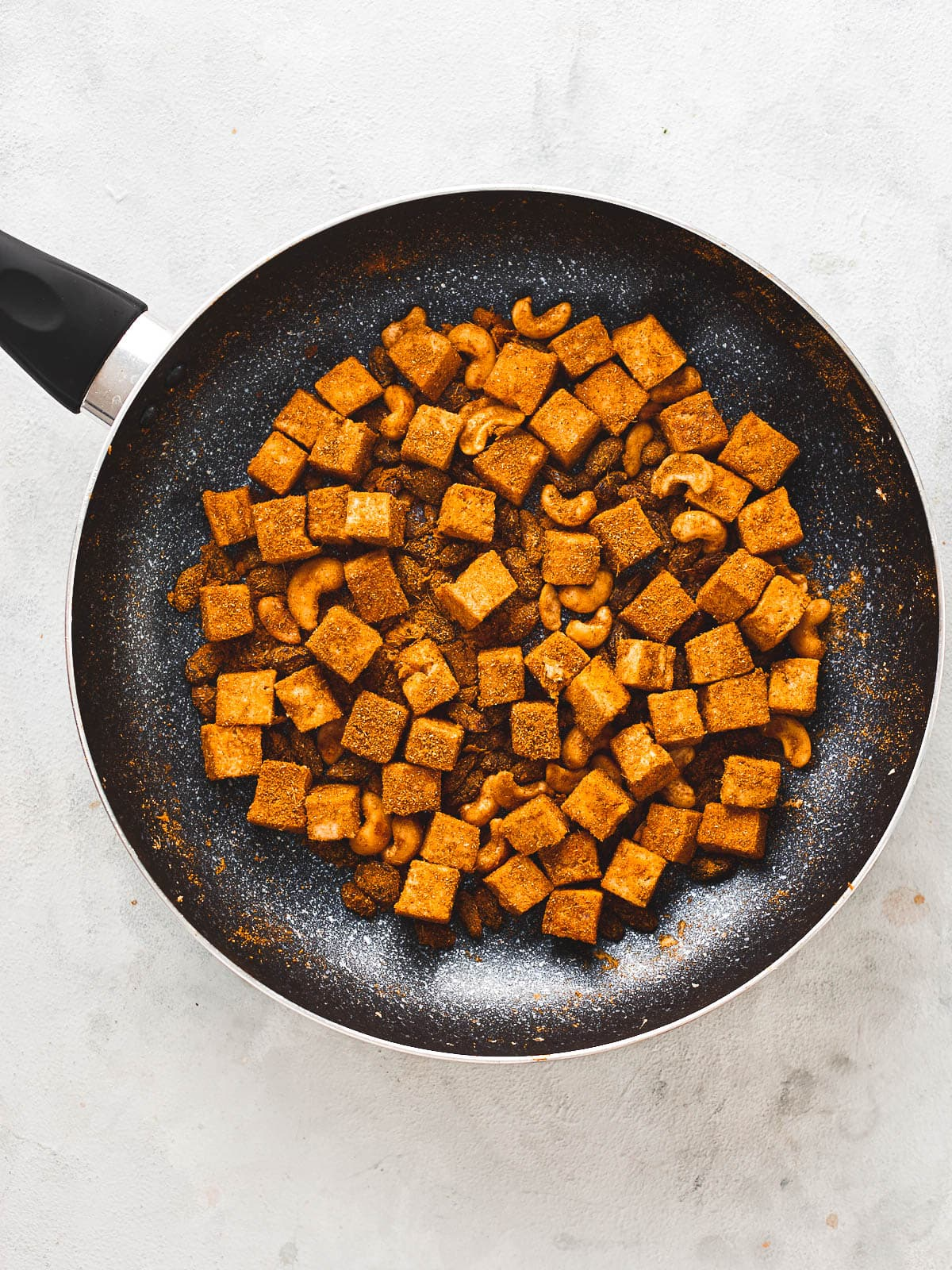 Spices stirred around and toasted with the tofu, cashews and raisins