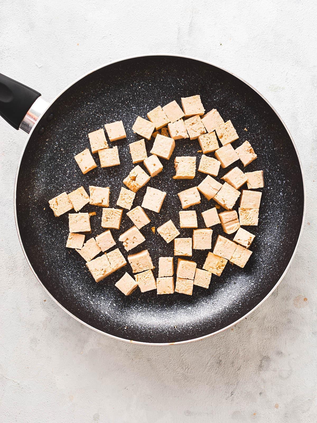 Cubed tofu in frying pan
