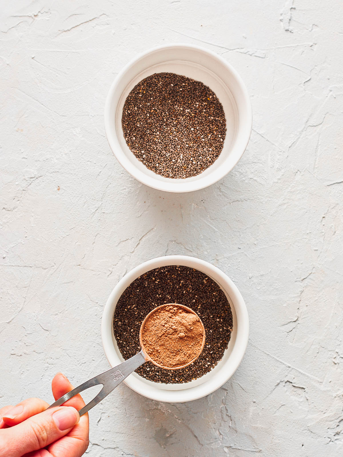 Adding cacao powder to one bowl of chia seeds