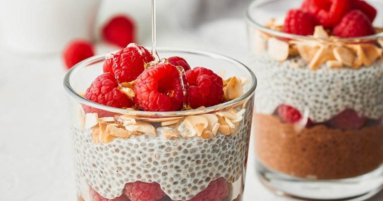Two glasses of chia seed parfait, a small bowl of raspberries, with a drizzle of agave