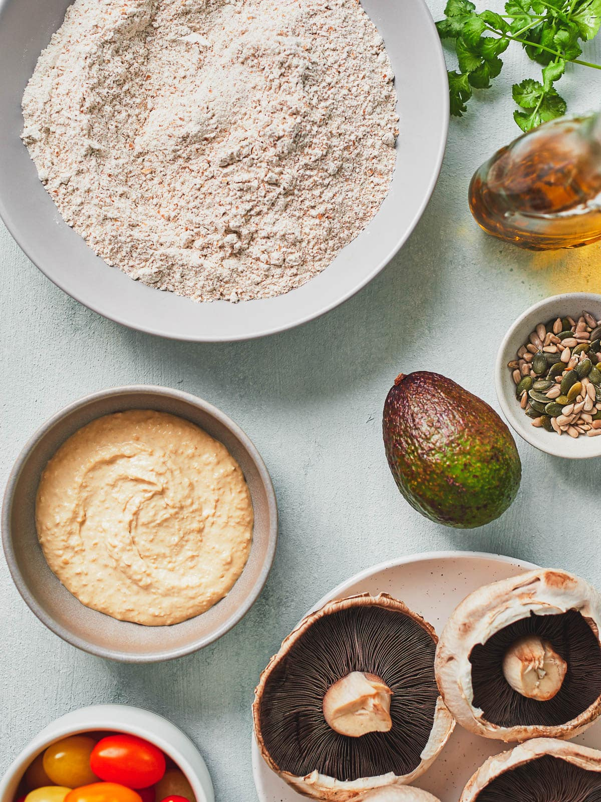Ingredients for hummus bread- flour, baking powder and salt, hummus, olive oil, mushrooms, tomatoes, avocado, seeds and herbs