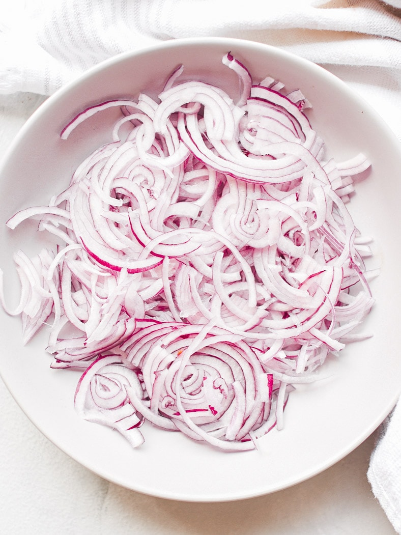 Raw sliced red onions in a bowl