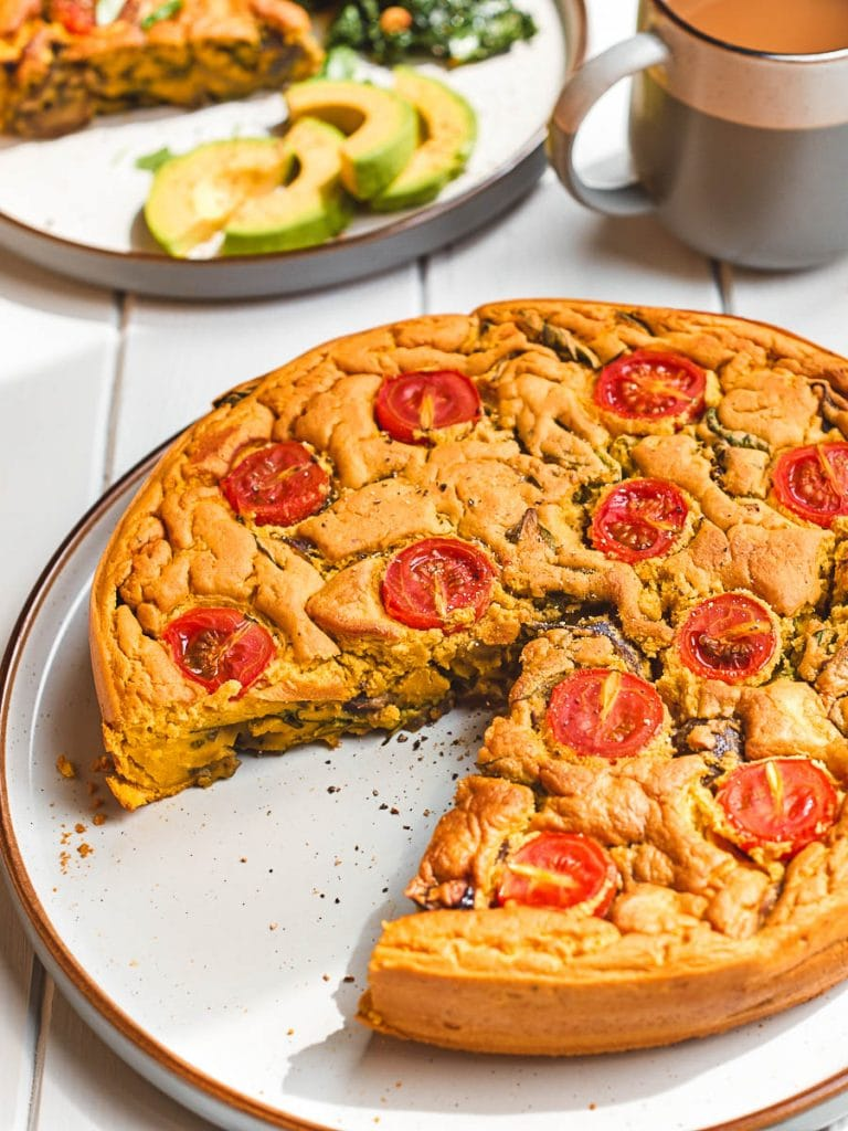Whole vegan frittata with a slice taken out of it
