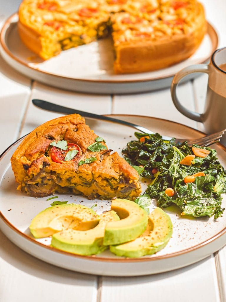 A slice of vegan frittata on a plate with sauteed kale and avocado
