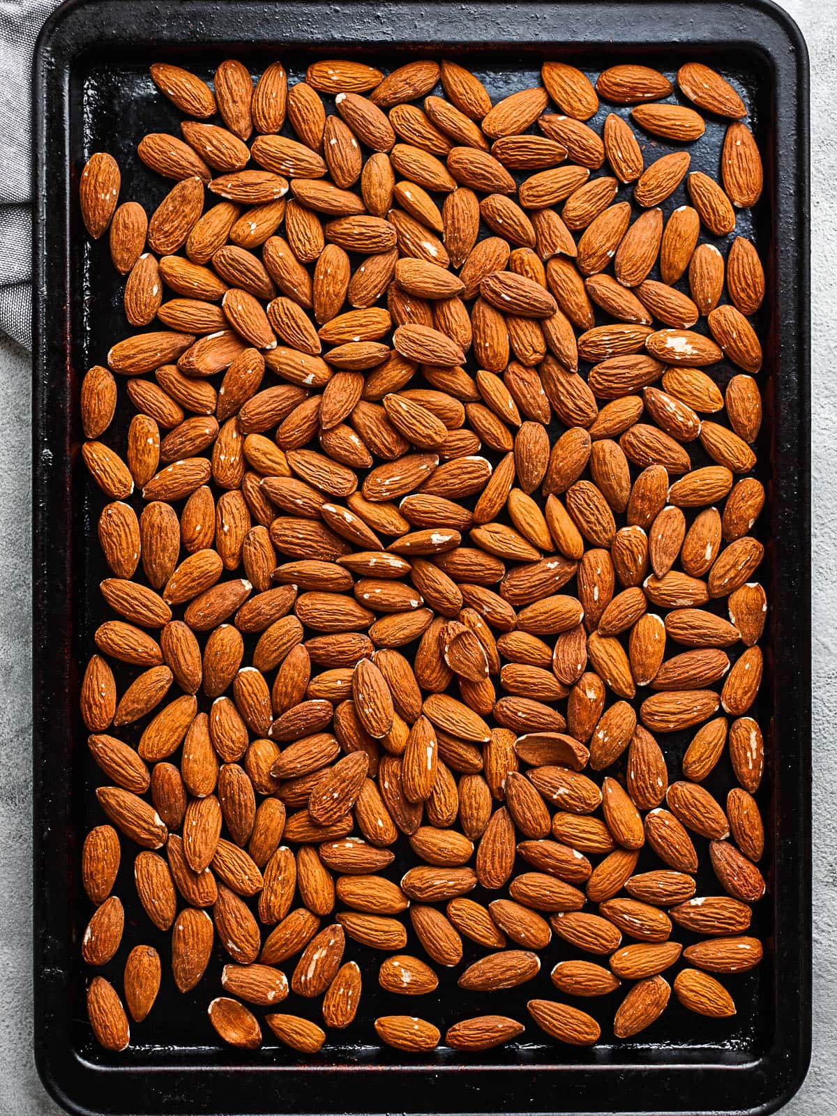 Almonds on a baking sheet before roasting