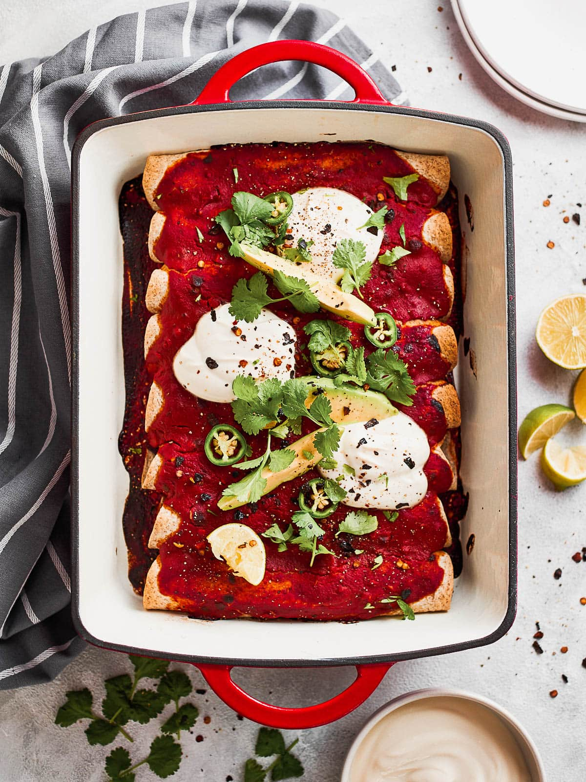 Overhead photograph of a casserole dish with jackfruit enchiladas in it, topped with avocado, yoghurt and cilantro