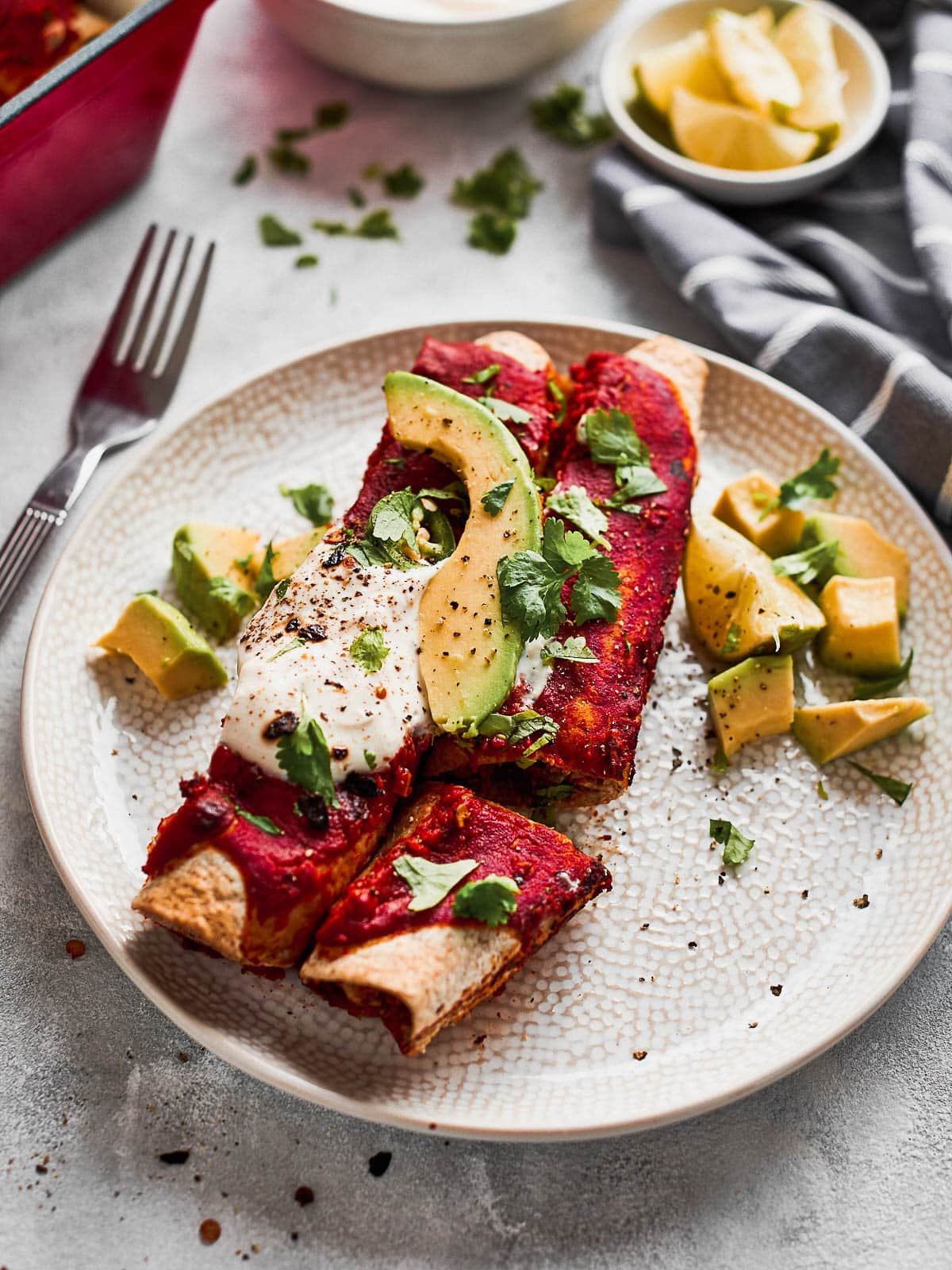 Two jackfruit enchiladas served up on a plate with avocado