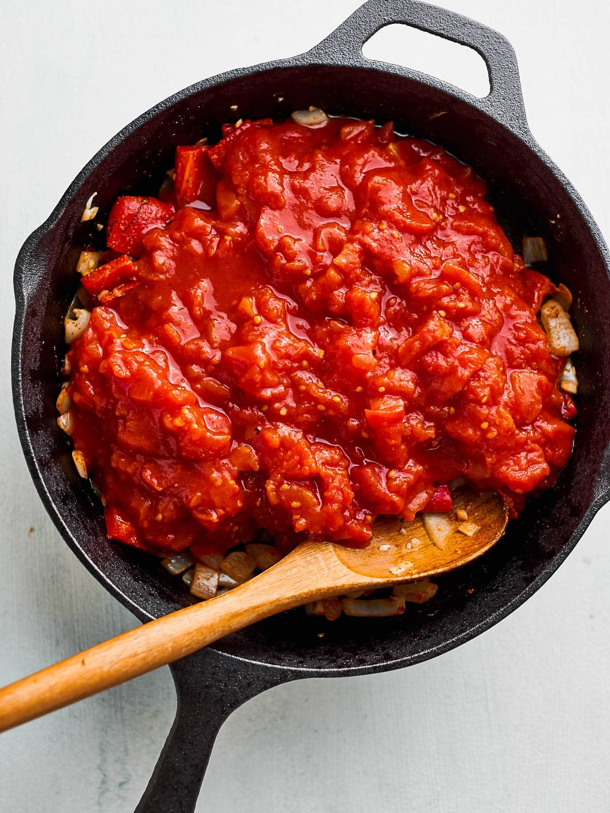 Chopped tomatoes have been added to the skillet