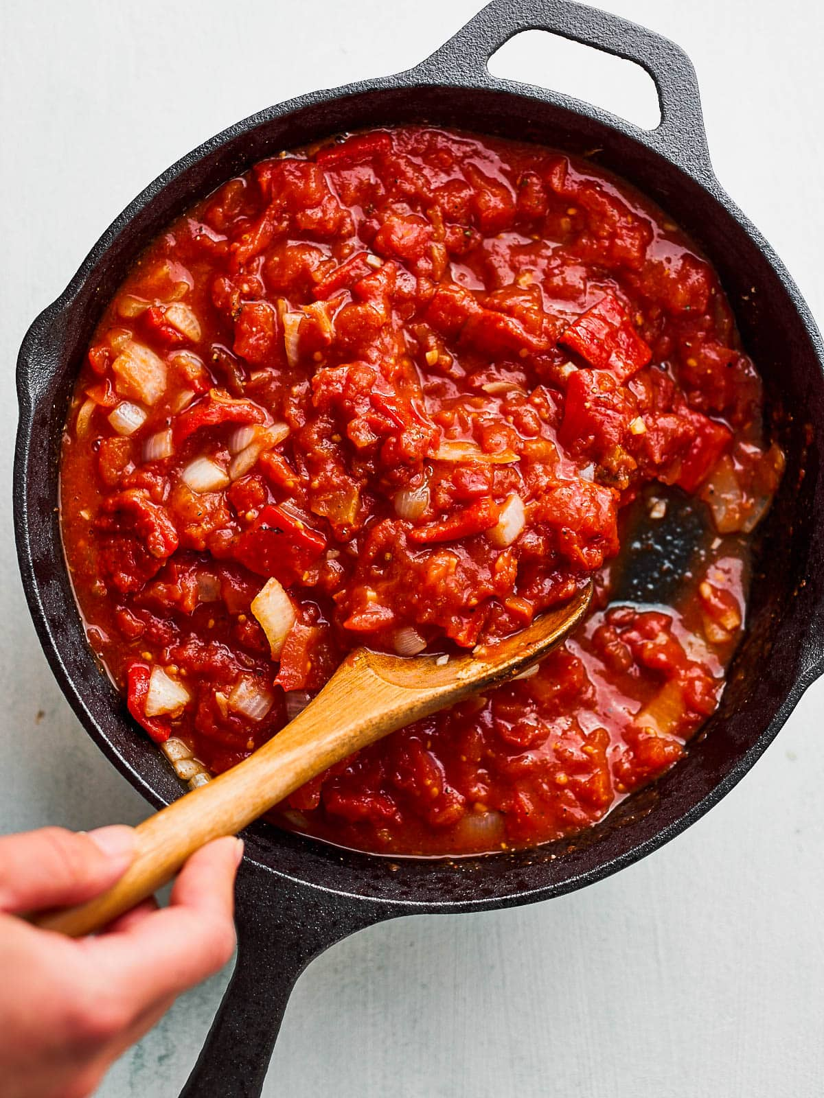 Shakshuka sauce is stirred and then simmered