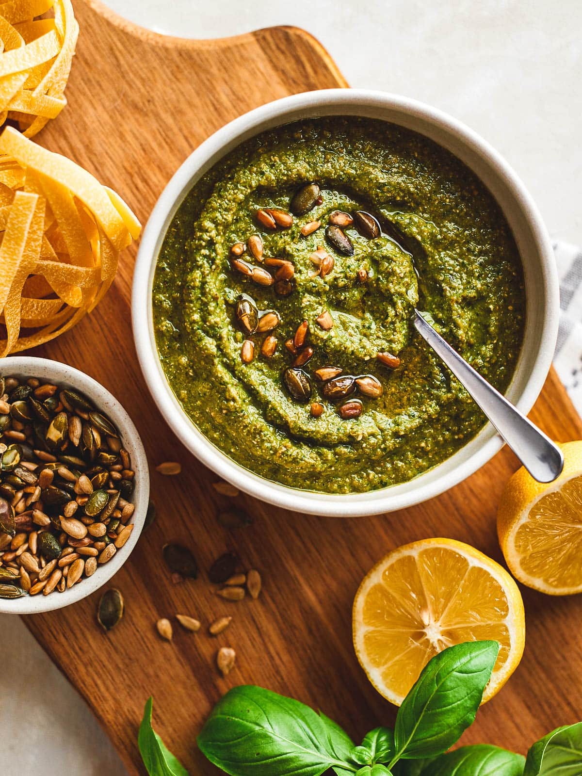 Zucchini pesto in a bowl with ingredients around it