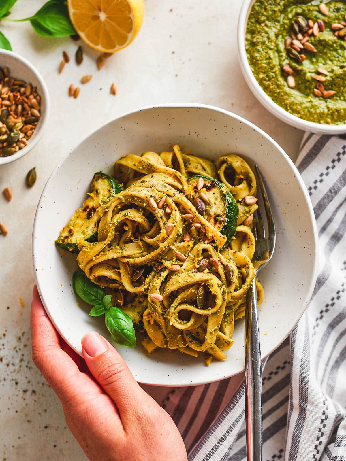 A hand taking a bowl of courgette pesto pasta
