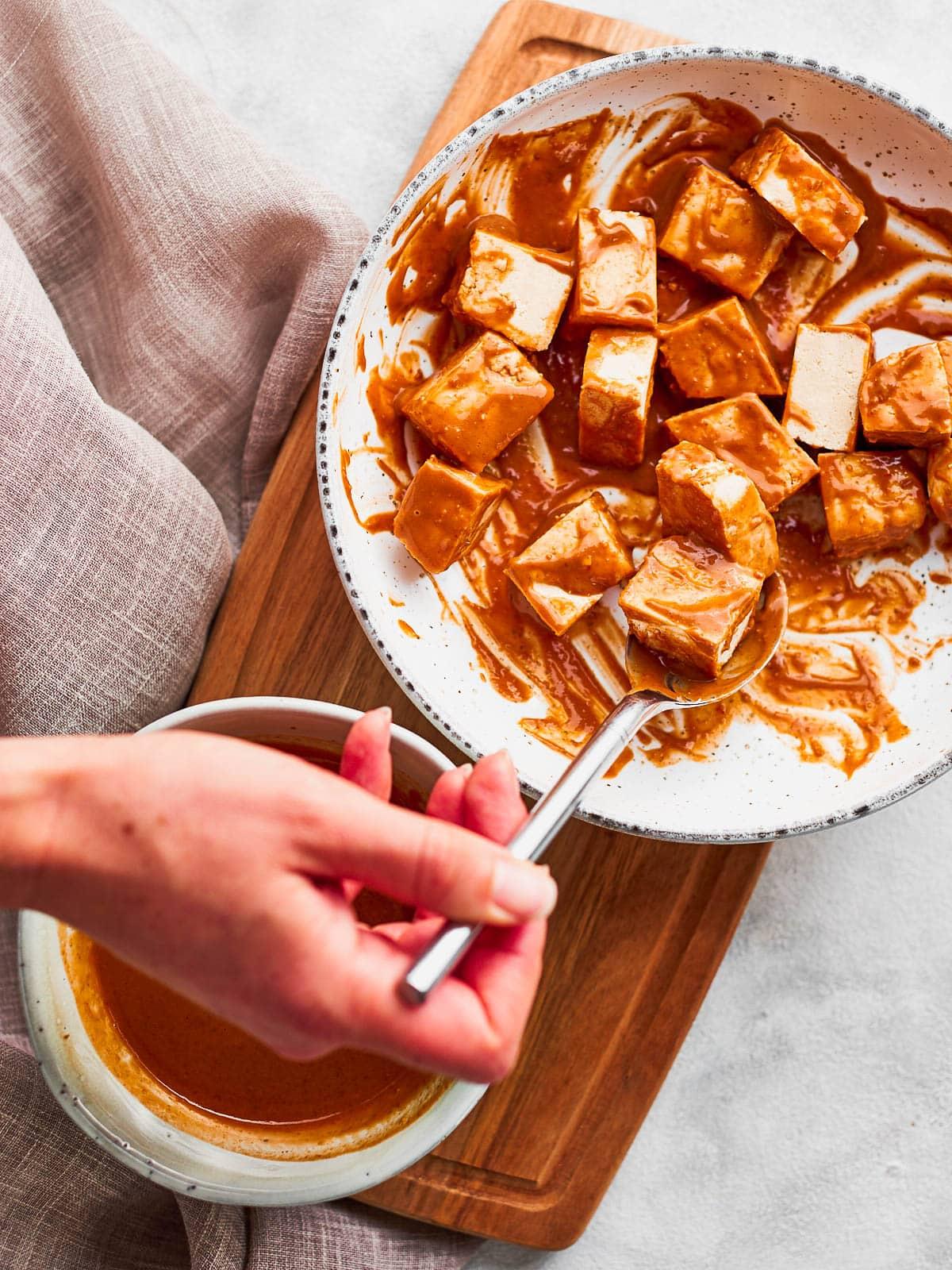 mixing the sauce through the tofu